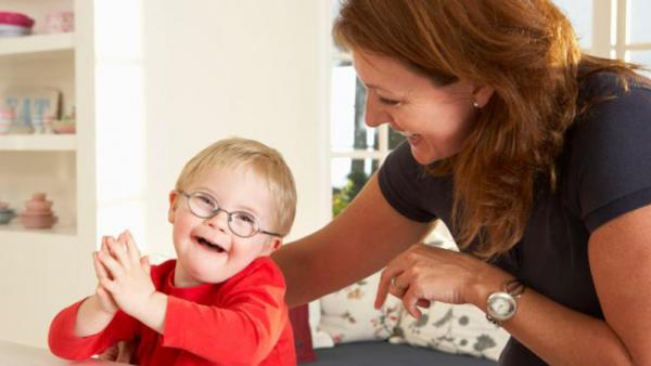 young happy child with developmental disability with caregiver